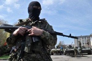 Armed men wearing military fatigues gather by Armored Personnel Carriers (APC) as they stand guard outside the regional state building seized by pro-Russian separatists in the eastern Ukrainian city of Slavyansk on April 16, 2014.